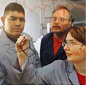 PECASE recipient Eugene Billiot and two students work on molecular structures.
