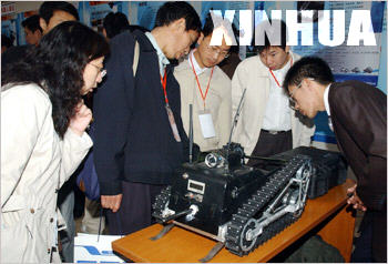 Teachers view a detective robot during the Robot Teaching and Research Seminar of Chinese Colleges and Universities in Beijing