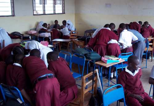 Tanzania students in classroom using microscopes