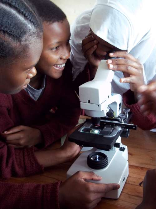 Students in Tazania using a microscope