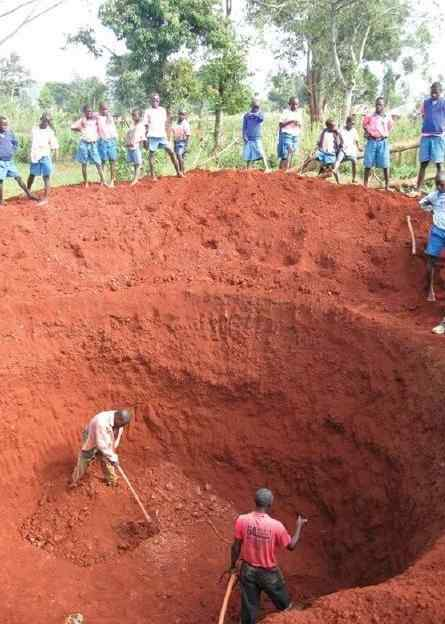 photo of workers digging a large hole dug for the bio-gas latrine, while schoolchildren look on.