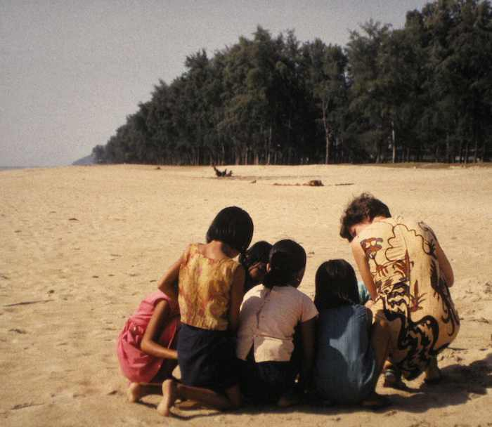 Photo of kids intently studying on a Malaysian beach