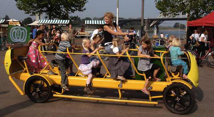 photo of kindergarden students pedaling their bus to school