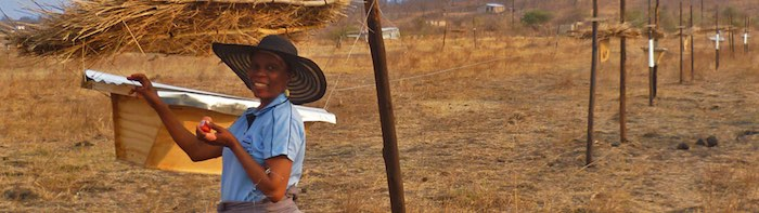 photo of farmer in front of beehive fence in Botswana